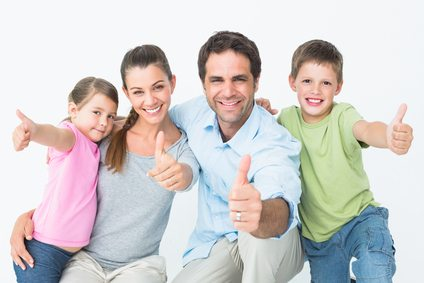 Cute family smiling at camera together showing thumbs up on white background